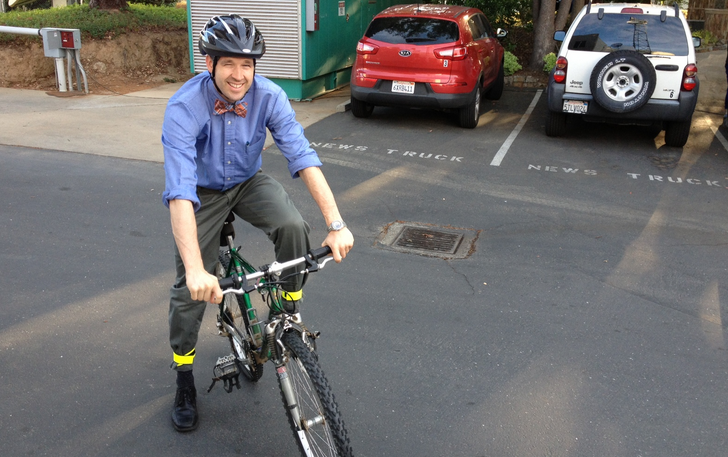 Former KTXL News Director Brandon Mercer rides a bike in the station's parking lot. (KTXL photo)