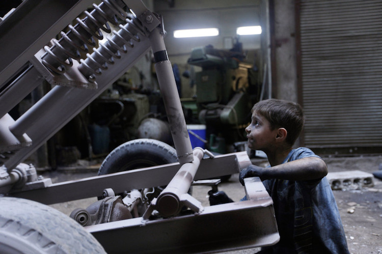Photography experts say this image of a boy at a bomb factory in Syria may have been staged. Reporters and photographers have tried to locate the boy in this image to no avail. [Photo: Hamid Khatib / Reuters, republished under 17 USC § 107]
