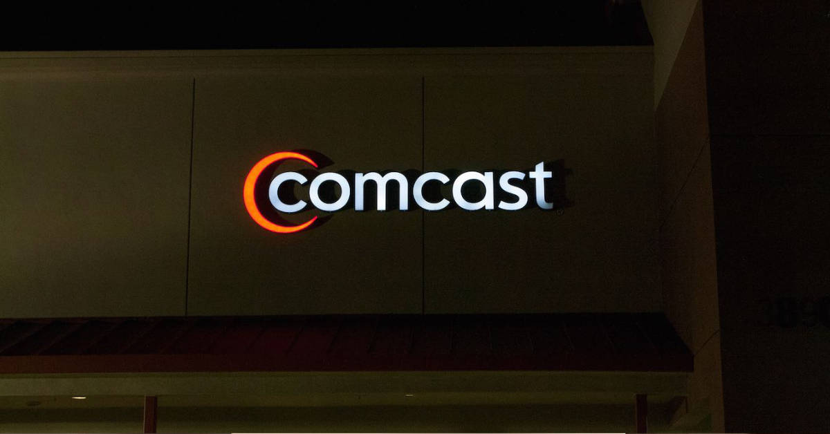 A picture of the Comcast logo on the front facade of a retail building.